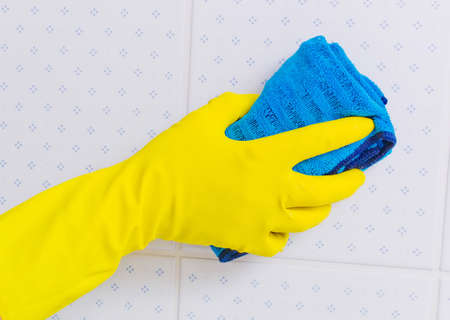 putz: the tiles of a bathroom is cleaned with latex gloves.