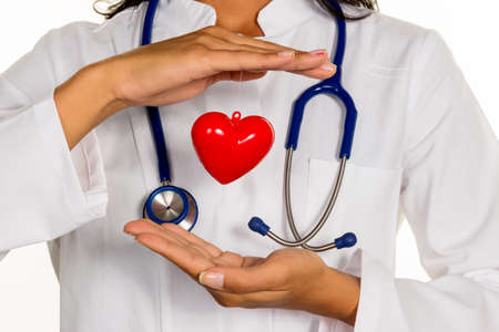 symbolically: a young doctor (internist) holding a heart symbolically in hand. Stock Photo