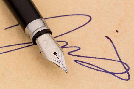 testament schreiben: eine Signatur und einem F�llfederhalter auf gelbem Papier. Symbolfoto f�r Vertrag, Zeugnis und Graphologie Lizenzfreie Bilder