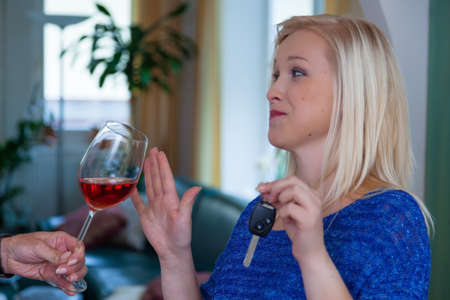 a young woman with car keys denied a glass of wine. do not drink and drive Stock Photo