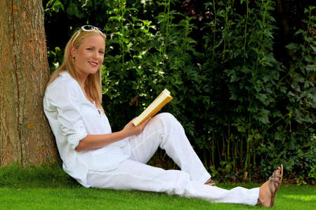 freetime activity: a young woman sitting in a meadow and reading a book. recreation in the park.