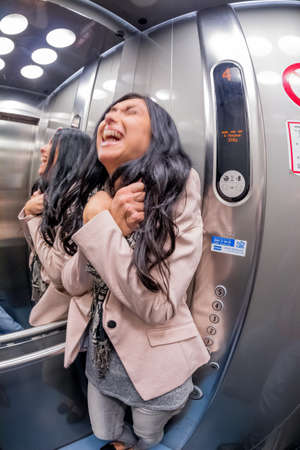 claustrophobia: a young woman with claustrophobia in an elevator