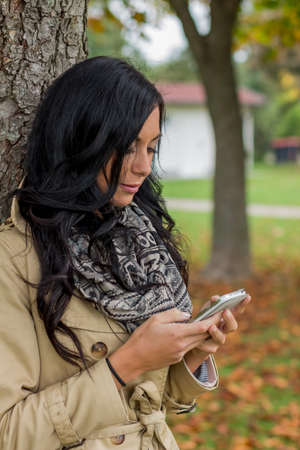 a young woman writes a text message on his cell phone. communication with a smart phone photo