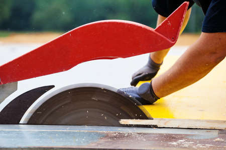 a construction worker cuts wood for shuttering on a construction site photo