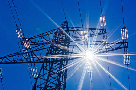 power lines: a high voltage towers for power against blue sky and sun rays Stock Photo