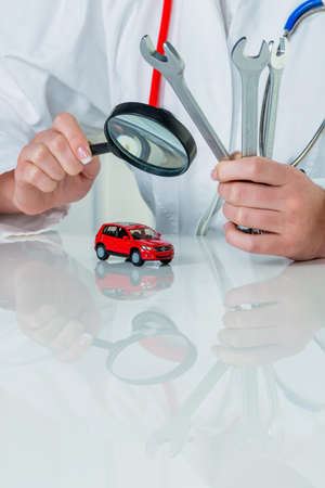 fully comprehensive: a model of a car is examined by a doctor. symbolic photo for workshop, service and car purchase.