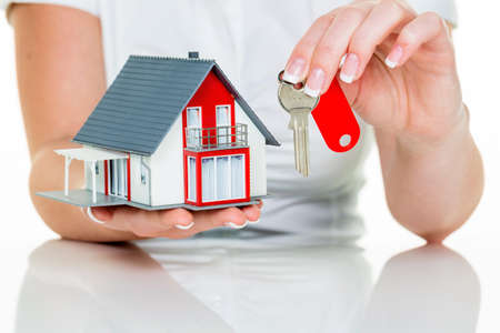 single familiy: an agent for property with a house and a key. successful leasing and property sales by real estate brokers. Stock Photo