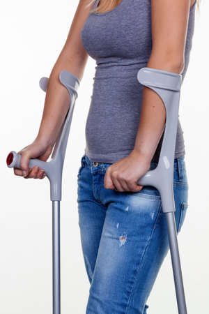 plaster foot: a young woman with crutches. symbolic photo for accidents, domestic accidents and insurance. Stock Photo