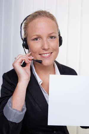 een vriendelijke jonge vrouw met hoofdtelefoon in de klantenservice aan de telefoon met een klant. vriendelijke hotline werknemer. Stockfoto