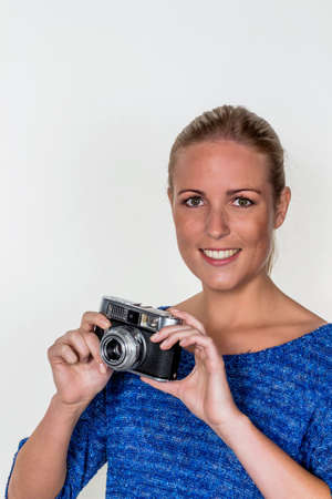 vivre: a young woman with an old camera. cameras with a retro look in again. Stock Photo