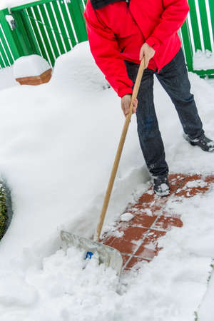 homeowners: a man shoveling snow from a new way. onset of winter Stock Photo
