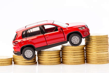 pkw: car standing on a stack of coins. symbol for car costs and fuel prices Stock Photo