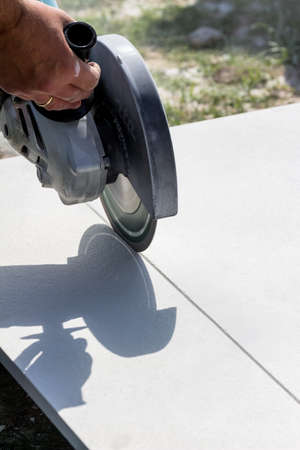 cutoff: a tiler at work. cuts plates with a cut-off wheel