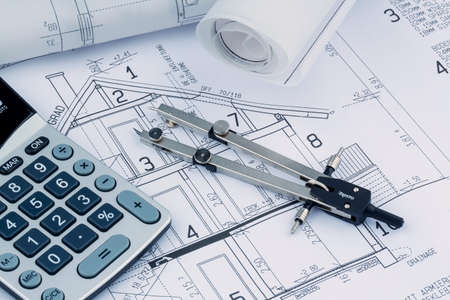 single familiy: a blueprint of an architect with a calculator. symbolic photo for financing and planning of a new house.