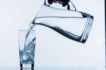 Agua pura se vacía en un vaso de agua de una jarra. agua potable Foto de archivo - 39798692
