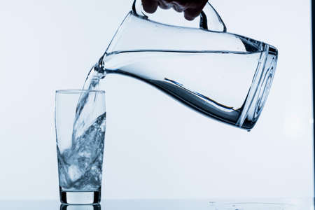 pure water is emptied into a glass of water from a jug. fresh drinking water