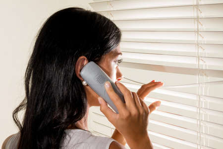 through the window: a young woman watching something through the blinds of her window Stock Photo