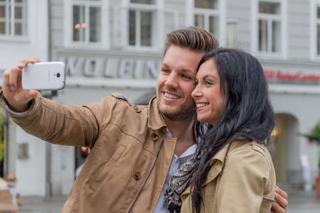 dear: a young couple making a self portrait with a mobile phone. selfies are in.
