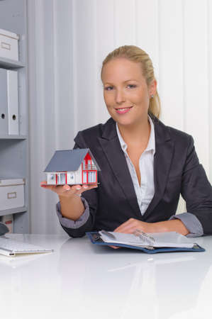 additional: a young real estate agent with a model house in her office.