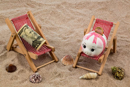 holiday profits: deckchair with dollars on the sandy beach. symbol photo for costs in travel, vacation, holiday. save on holiday