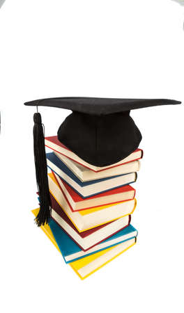 a mortar board on a pile of books, symbolfoto of education and competence photo