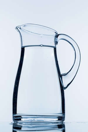 potable: a pitcher of water against white background, symbol photo for drinking water, water demand and consumption