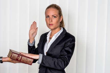 dagvaarding: een vrouw zegt dat als getuige in de rechtbank in een rechtszaak. zal worden beëdigd en zweert op de bijbel.