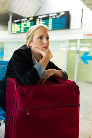impatience: businesswoman waiting for her departure at the airport. symbolic photo for delays, flight cancellations and strikes.