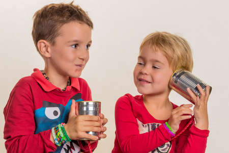 hark: two little children with a telephone call from two cans. Stock Photo