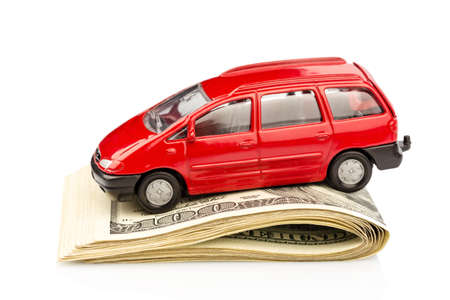 pkw: A car stands on dollar banknotes. costs for the purchase of automobiles, gasoline, insurance and other car costs Stock Photo