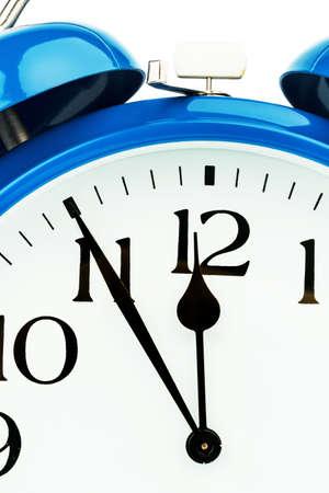 ultimatum: A blue alarm clock on a white . eleventh hour