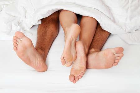 Ein paar Füße im Bett. Liebe, Erotik und Partnern.