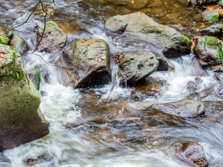 fluent: A creek with rocks and running water. landscape experience in nature. Stock Photo