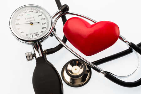 presure: A sphygmomanometer, a heart and stethoscope lying on a white ground Stock Photo