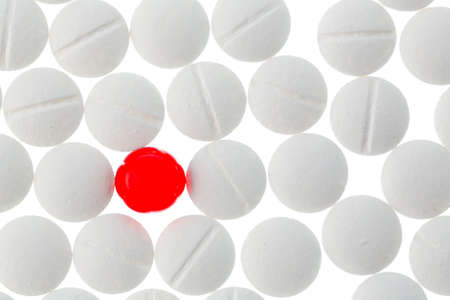 therapie: White tablets in contrast with a red tablet, symbol photo for bullying and individuality Stock Photo