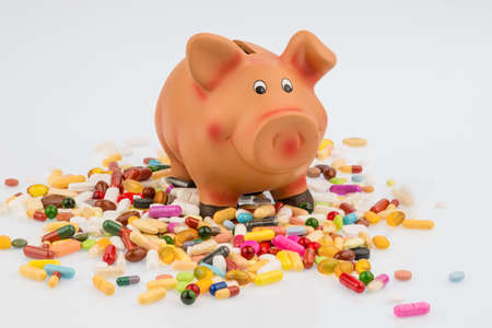 therapie: Tablets lying next to a piggy bank. symbol photo for costs in medicine and pharmaceutical industry
