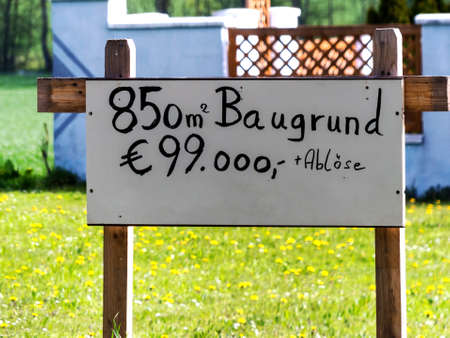 immobilien: On a meadow there is a sign land for house for sale. site for a new home.