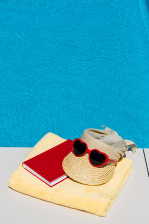 utensils for a nice relaxing vacation day lying next to a swimming pool. relaxation on vacation. Stock Photo