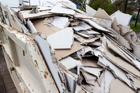plasterboard: in a waste container stacks sheets of plasterboard for their disposal
