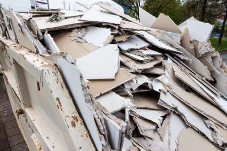 in een afvalcontainer stapels bladen van gipsplaten voor de verwijdering ervan Stockfoto