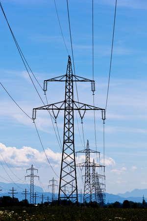 torres el�ctricas: pilones un alto voltaje de la electricidad contra un cielo azul. Foto de archivo
