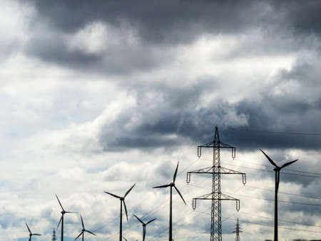 energy needs: wind turbines and electricity pylons in a wind farm. wind-power plant for renewable energy.