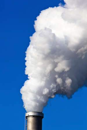 smokestacks: the smokestacks of a factory against a blue sky. rises from chimneys white smoke on
