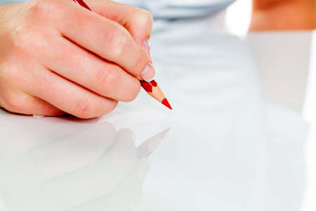 cheaper: a hand holding a red pen. symbolic photo for savings and budegt cuts.