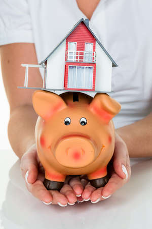 single familiy: a woman with a house and a piggy bank. proper funding for the home purchase.