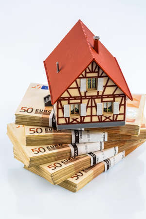 immobilien: half-timbered house on euro banknotes, symbol photo for home purchase, financing, building society