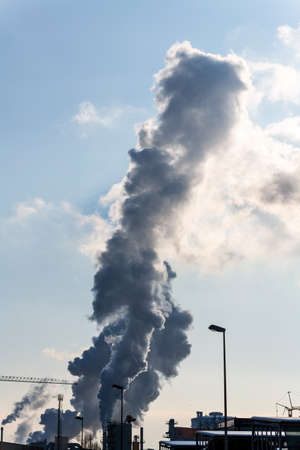 emissions: chimney of an industrial company with smoke. symbolic photo for environmental protection and ozone.