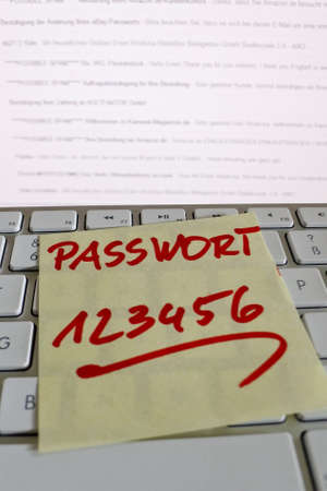 notieren: a memo is on the keyboard of a computer as a reminder: password 123456
