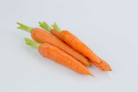 organically: organically grown carrots lying on white background. fresh vegetables and fruits is always healthy. Stock Photo
