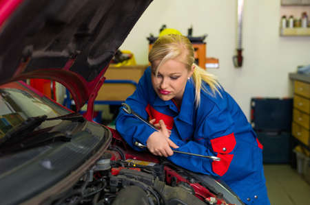 pkw: a young woman as a mechanic in an auto repair shop. rare occupations for women. car will be repaired in workshop